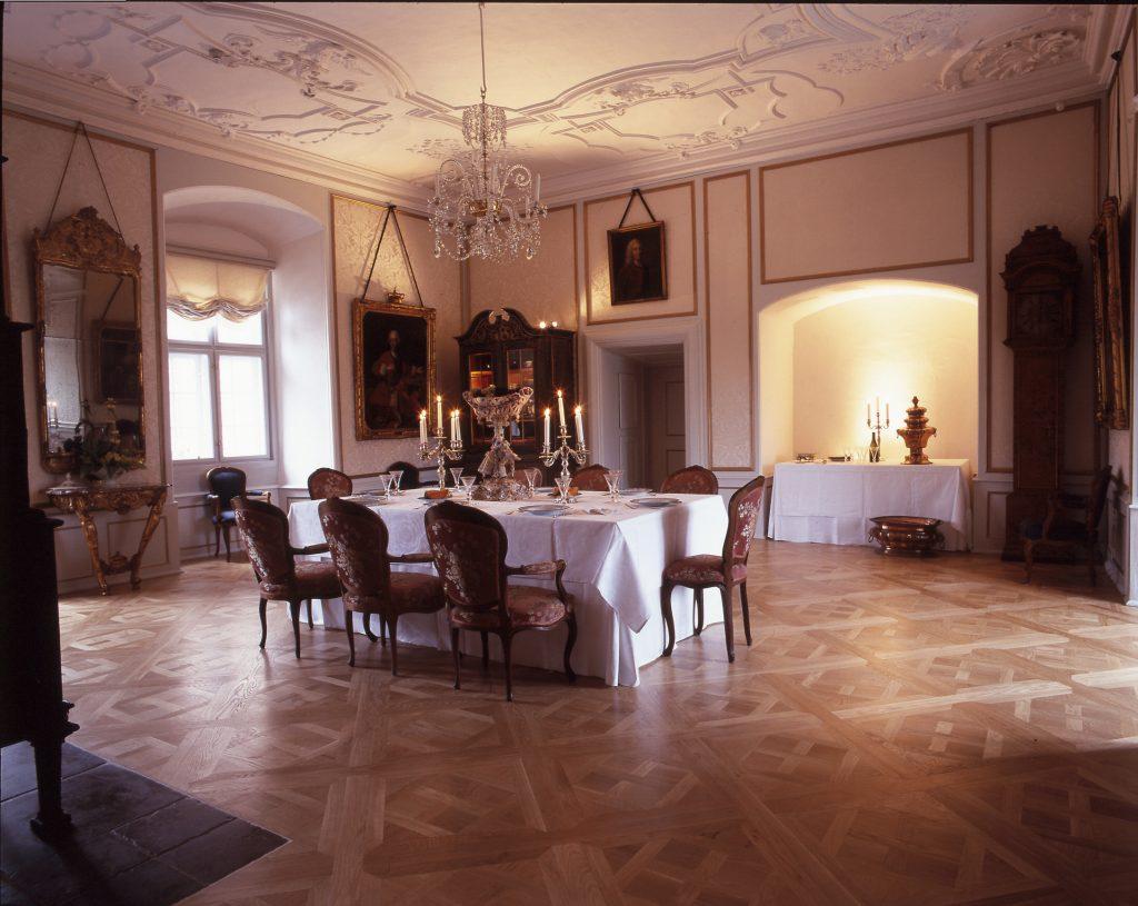 Spisesalen på Gammel Estrup er indrettet tidstypisk i rokokoens lyse og lette farveskala. Parketgulve med kunstfærdigt udformede mønstre var højeste mode i midten af 1700-tallet og det samme gør sig gældende for det store konsolspejl til venstre i billedet. Foto: Gammel Estrup – Herregårdsmuseet.