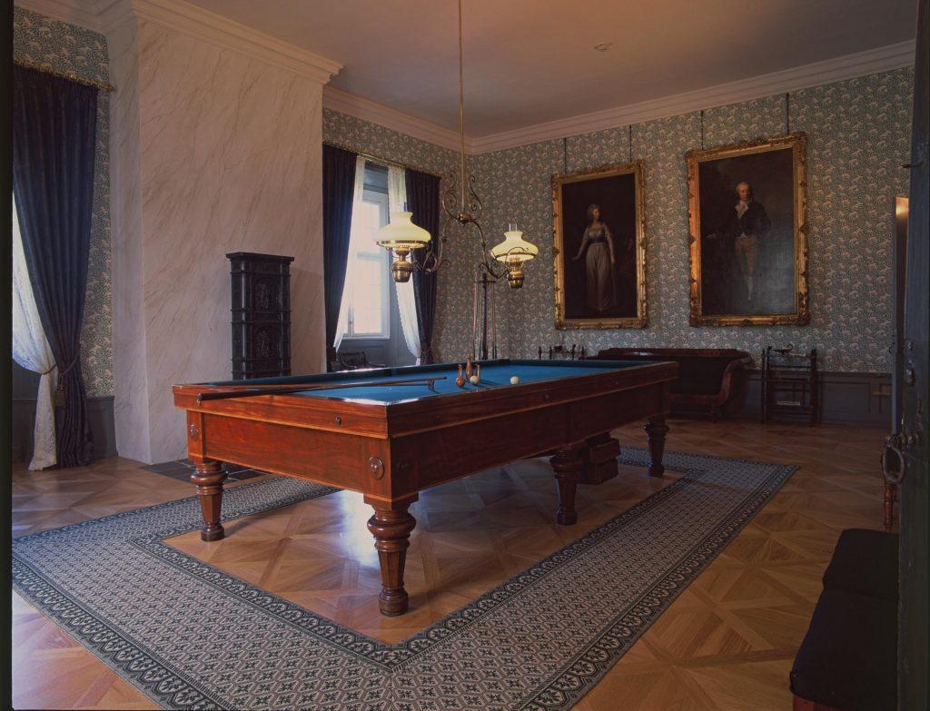 Christen Scheel og Christiane Pind blev gift i 1827, og dermed fik Gammel Estrup igen et ejerpar som boede på herregården. I stil med deres forgængere gennemførte parret en nyindretning af den gamle herregård, så Gammel Estrup kunne fremstå som en passende, herskabelig bolig i tidens stil. I Gammel Estrup – Herregårdsmuseets nyindretning fra 2015, blev der atter indrettet billardsal i hjørneværelset på anden sal. Foto: Gammel Estrup – Herregårdsmuseet.