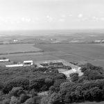 På dette foto fra 1961 er det er ikke til at se det, hvis man ikke lige ved det. Billedet er taget i en tid, hvor eng blev drænet og indvundet til agerland, men områderne nord for Lønborggård (højre halvdel af dette foto) var eng i århundreder. Efter naturgenopretning omkring år 2000 er området ført tilbage til den gamle tilstand. Foto: Sylvest Jensen, Det Kongelige Bibliotek.