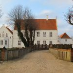 Borggårdens statelige østfløj kaldes Gyldenstjernehuset efter bygherren, rigsråd Predbjørn Gyldenstjerne, der lod huset opføre omkring 1575 som bolig for sig og sin familie. Det grundmurede, toetages hus er herregårdens ældste bevarede bygning, og gennem århundrederne har det undergået flere ombygninger. På et tidspunkt var stueetagen gennembrudt af en køreport, der gav adgang til gårdspladsen, men i forbindelse med Peder Tangs ombygning af huset i slutningen af 1790'erne blev porten nedlagt. De fire gamle lindetræer mellem broen og huset er rester af en allé, der førte frem til porten. Set mod vest. Foto. Helle Henningsen.