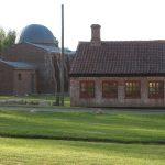 """Der er ikke bevaret mange synlige spor efter den megen aktivitet, der herskede på Skærum Mølle i årtierne omkring år 1900. Det lille røde hus, der ligger ud til vejen, var dog engang en del af den store virksomhed. I dag huser det et lille teglværksmuseum. Bag huset ses Per Kirkebys monumentale teglstensskulptur """"Huset for sten og stjerner"""", der er opført i 1996 og bekostet af Ny Carlsberg Fondet. Foto: Helle Henningsen."""