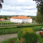 Den imponerende hovedbygning på Clausholm gods blev opført i 1690'erne af storkansler Conrad Reventlow, hvis marmorbuste fortsat findes over indgangspartiet. Det trefløjede barokanlæg blev i 1718 overtaget af Frederik IV, der mod syd tilføjede de to udløberfløje, der her ses på billedet. Ved samme lejlighed fik Clausholm sin nuværende farve, idet de oprindelige røde pudsede mure blev kalket hvide. Foto: Bent Olsen